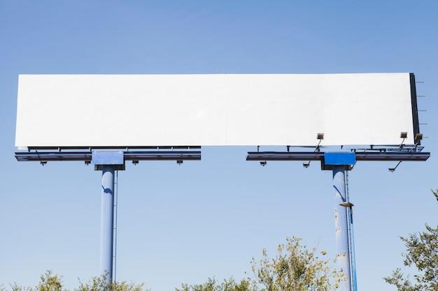 Gran valla publicitaria en blanco sobre fondo azul.