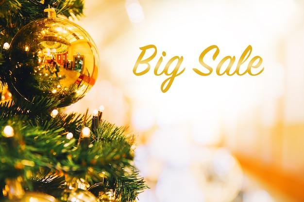 Gran venta de bolas de oro de navidad colgando de un árbol de navidad