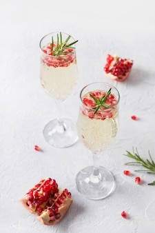 Granada cóctel de navidad con romero, vino espumoso en mesa blanca. bebida navideña.