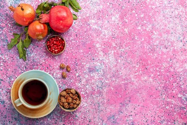 Granada fresca vista superior con hojas verdes y taza de té en la superficie rosa