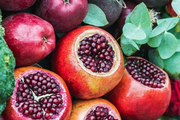 Granada fruta madura, manzana y rosas hermosas en naturaleza muerta