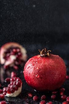 Granada de jugo rojo en la mesa oscura. granada útil