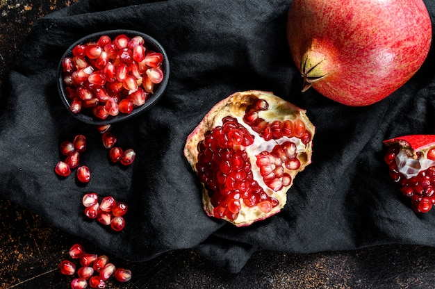 Granada roja madura. fruta orgánica fondo negro. vista superior.