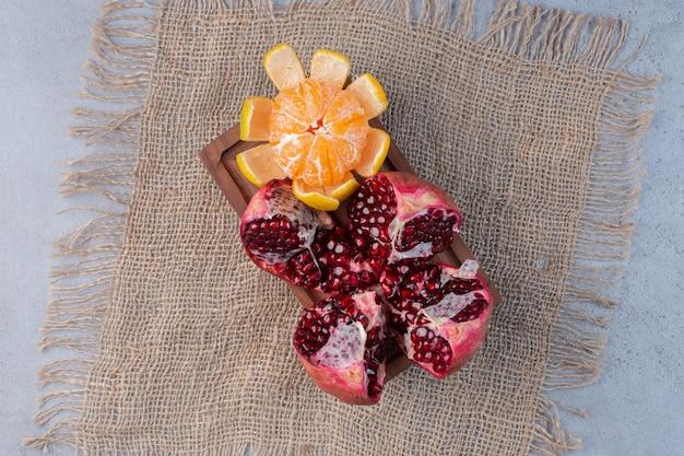 Una granada rota y una mandarina pelada sobre un trozo de tela sobre fondo de mármol.