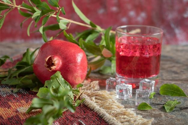 Granada y vaso de jugo en la mesa de piedra con hojas