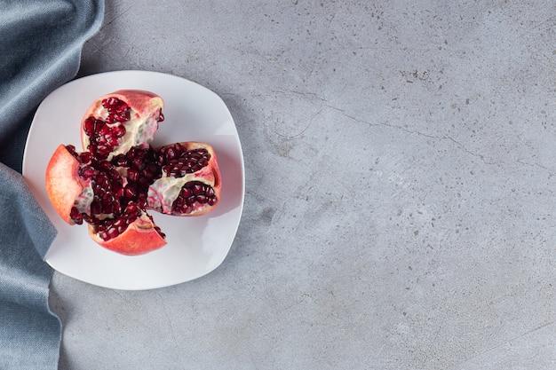 Granadas maduras frescas con semillas colocadas en un plato blanco.