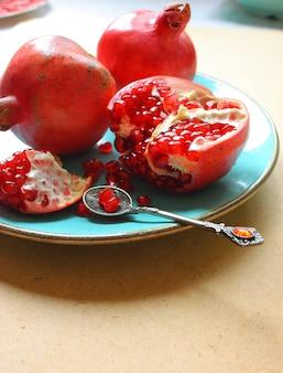 Granadas rojas enteras y cortadas en el plato
