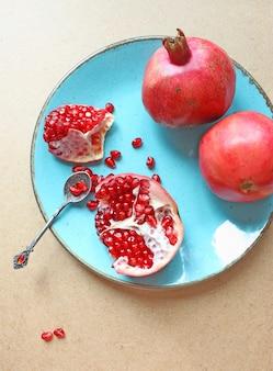 Granadas rojas en un plato azul