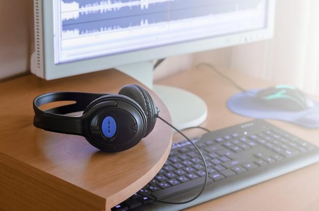 Grandes auriculares negros se encuentran en el escritorio de madera del diseñador de sonido