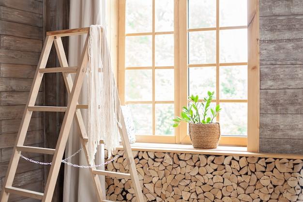 Grandes claraboyas con adornos de madera, cortinas y escalera de tijera. la planta de la casa zamioculcas en una maceta de paja se alza sobre un alféizar. hygge boho interior rústico escandinavo. espacio para texto
