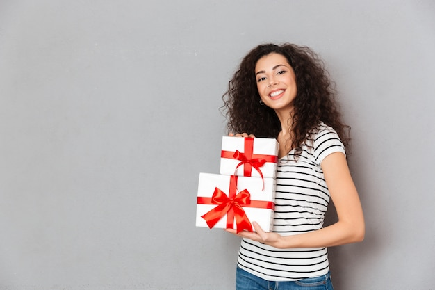 Grandes emociones de mujer joven en camiseta a rayas con dos cajas envueltas en regalos con lazos rojos mientras está de pie sobre la pared gris