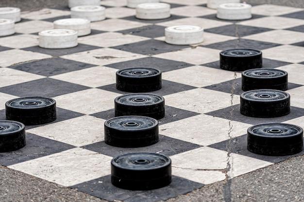 Grandes fichas de plástico pintadas en las celdas del pavimento en un parque de la ciudad