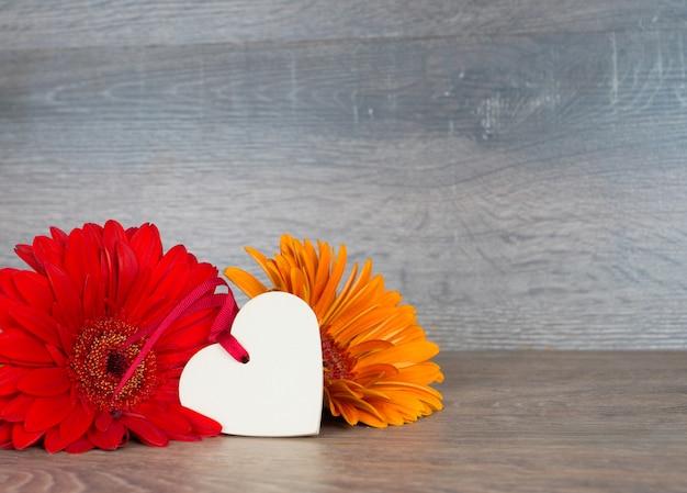Grandes flores rojas y naranjas con forma de corazón en la mesa de madera rústica