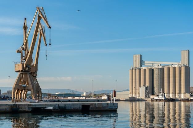 Grandes grúas portuarias con silos al fondo.
