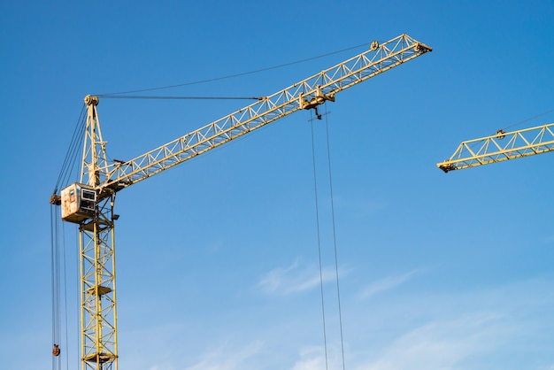 Grandes grúas torre contra el cielo azul. imagen de fondo de primer plano de equipo de construcción con espacio de copia. construir de ciudad.