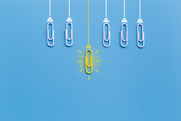 Grandes ideas con clip, pensamiento, creatividad, bombilla sobre fondo azul, nuevas ideas
