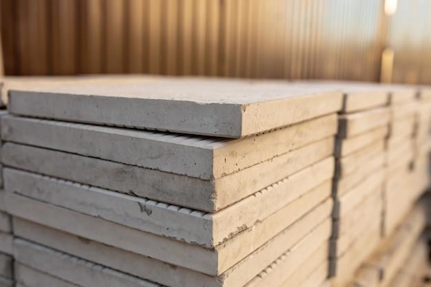 Grandes losas cuadradas en la pila en el sitio de construcción de la entrada del patio trasero o el pavimento de la acera