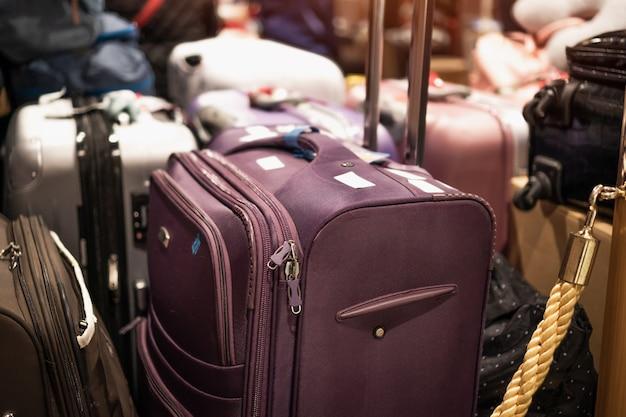 Grandes maletas negras o equipaje en la sala de espera del hotel del vestíbulo con destellos de luz.