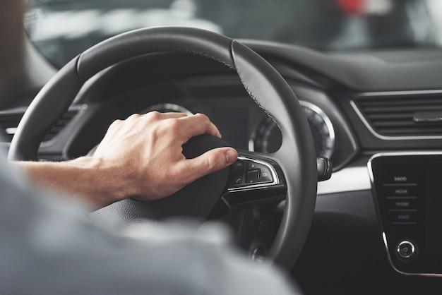 Grandes manos del hombre en un volante mientras conduce un coche.