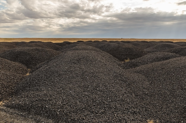 Grandes montones de asfalto viejo en la estepa después de la reparación de carreteras kazajstán