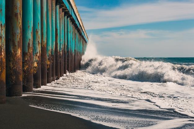 Grandes olas rompen en el muelle, una tormenta en el océano