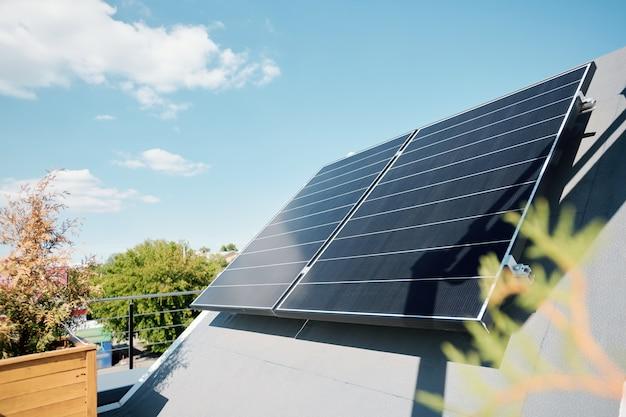 Grandes paneles solares en la azotea de una casa o cabaña moderna y cómoda en un entorno natural