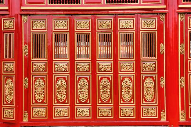 Las grandes puertas de madera talladas en rojo en el palacio hue.