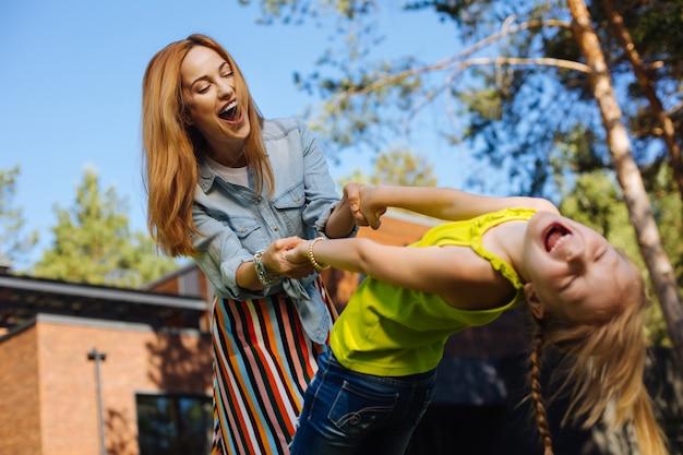 Grandes relaciones. amorosa madre rubia sonriendo y divirtiéndose con su hija