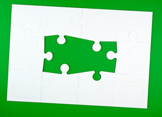 Grandes rompecabezas blancos en blanco sobre verde