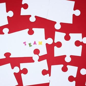 Grandes rompecabezas blancos sobre rojo, equipo de inscripción