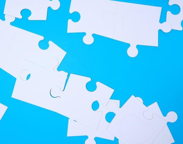 Grandes rompecabezas blancos vacíos sobre una superficie azul