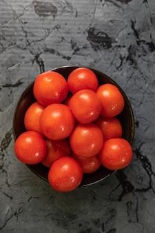 Grandes tomates rojos en un plato negro, sobre una mesa de granito