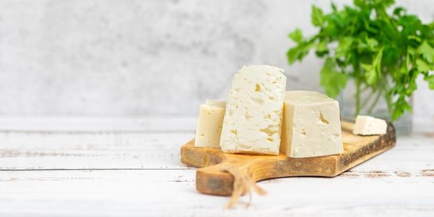 Grandes trozos de queso feta sobre tabla de cortar de madera vieja y perejil a la luz.