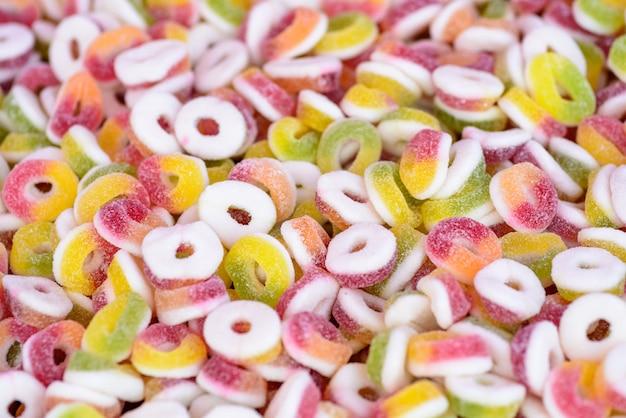 A granel de anillos de caramelo gomoso con sabor a frutas, fondo colorido