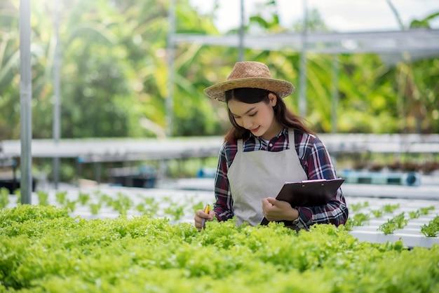Granja de vegetales hidropónicos. sonriente mujer asiática estudiando, examinando e investigando verduras de una granja hidropónica