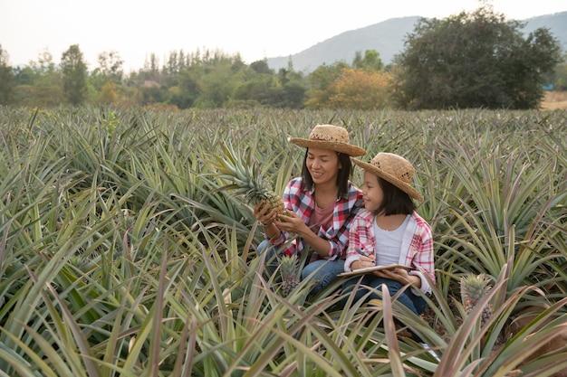 Granjero asiático hace que madre e hija vean el crecimiento de la piña en la granja y guarden los datos en la lista de verificación del granjero en su portapapeles, concepto de industria agrícola