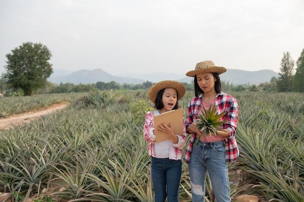 Granjero asiático hace que madre e hija vean el crecimiento de la piña en la granja y guarden los datos en la lista de verificación del granjero en su portapapeles