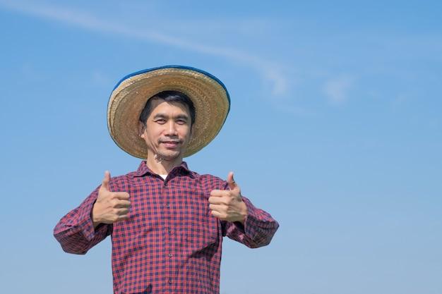 Granjero asiático hombre de pie y pulgar hacia arriba pose