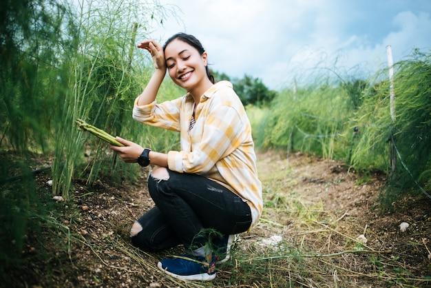 El granjero bonito joven cosecha el espárrago fresco con la mano en el campo.