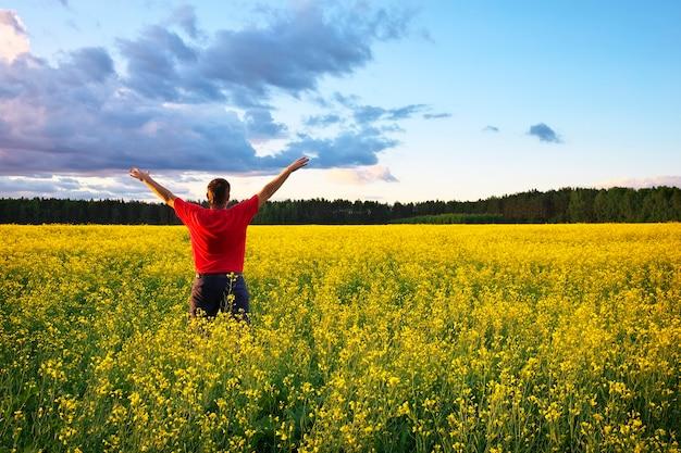 Granjero con brazo extendido en el campo de violación. hermoso paisaje con campo de colza amarilla (brassica napus l.) y cielo azul
