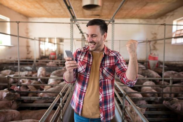 Granjero en el corral de cerdo con teléfono móvil recibiendo buenas noticias del banco que su préstamo ha sido aprobado