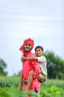 Granjero indio jugando con su hijo en el campo verde