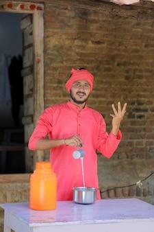 Granjero indio o lechero distribuir leche en la granja lechera