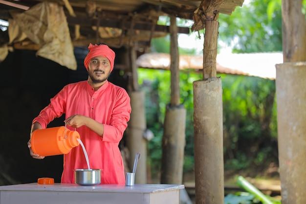 Granjero indio o lechero recogiendo leche en la granja lechera