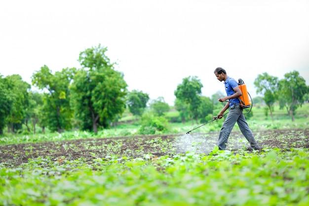 Granjero indio rociar pesticidas en el campo