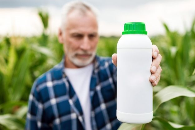 Granjero de mediana edad en un campo que muestra una botella con fertilizantes químicos.