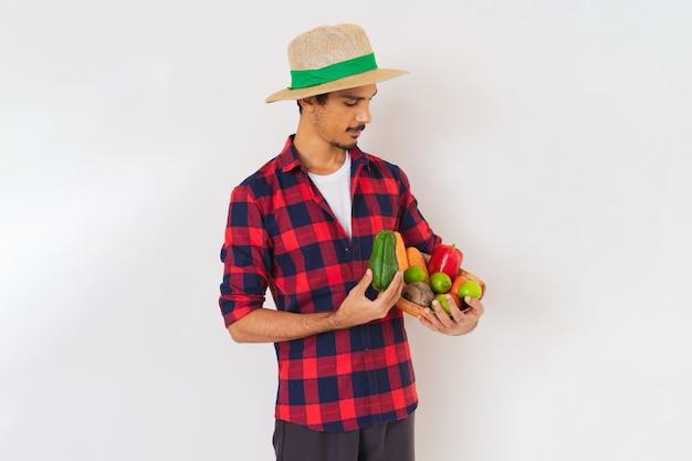 Granjero negro con sombrero y guantes sosteniendo una canasta de verduras (zanahoria, limón, tomate, chayote y remolacha) aislado en fondo blanco.