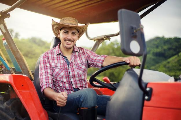 Granjero que conduce el tractor en los campos durante cosecha en campo.