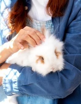 Granjero de sexo femenino que sostiene un conejito blanco