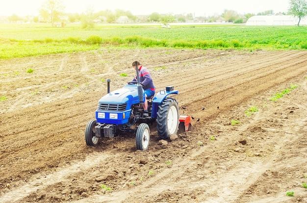 Un granjero en un tractor cultiva un campo agrícola.
